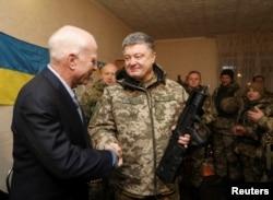 Ukrainian President Petro Poroshenko (R) shakes hands with U.S. Senator John McCain during a meeting with Ukrainian servicemen in Shirokino settlement near Mariupol, Ukraine, Dec. 31, 2016.