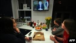 Una familia londinense escucha el mensaje del primer ministro Boris Johnson en el que anunció una cuarentena obligatoria en todo el país, siguiendo los pasos de Italia, España y Francia.