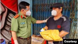 Ông Đinh Văn Nơi (trái) tặng quà cho người dân. (Hình: CTV via Thanhnien.vn)