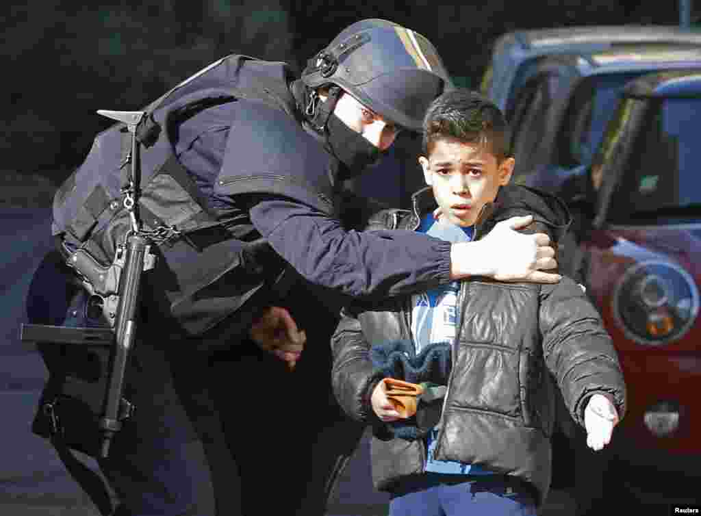 A French police officer speaks to a child as he secures an access to a school at the Castellane housing area in Marseille. Hooded gunmen armed with Kalashnikov rifles fired on police in the French city, where Prime Minister was paying a visit, a police source said.