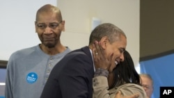 President Barack Obama is embraced by a volunteer as he visits a campaign office the morning of the 2012 election in Chicago, November 6, 2012.