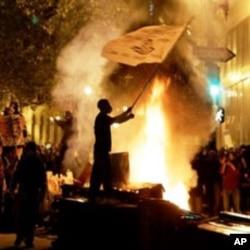 An Occupy Oakland protester waves a flag next to a bonfire in Oakland, California, November 3, 2011.