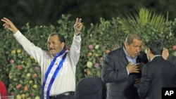 Nicaragua's President Daniel Ortega greets supporters at the swearing-in ceremony for his second term as president, with Venezuela's President Hugo Chavez (second right), at the Revolution Square in Managua, Nicaragua, January 10, 2012.