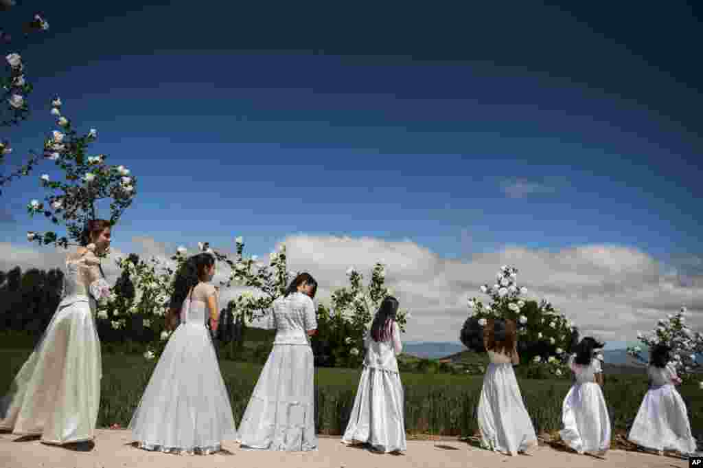 "Teenagers dressed in bridal white surrounded by flowers, take part in the pilgrimage ""The Hundred Maidens"", in Sorzano, northern Spain."