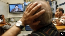 Lebanese watch Hezbollah's leader Hassan Nasrallah as he speaks in a televised address at a cafe in Beirut, Lebanon, Saturday, July 2, 2011.