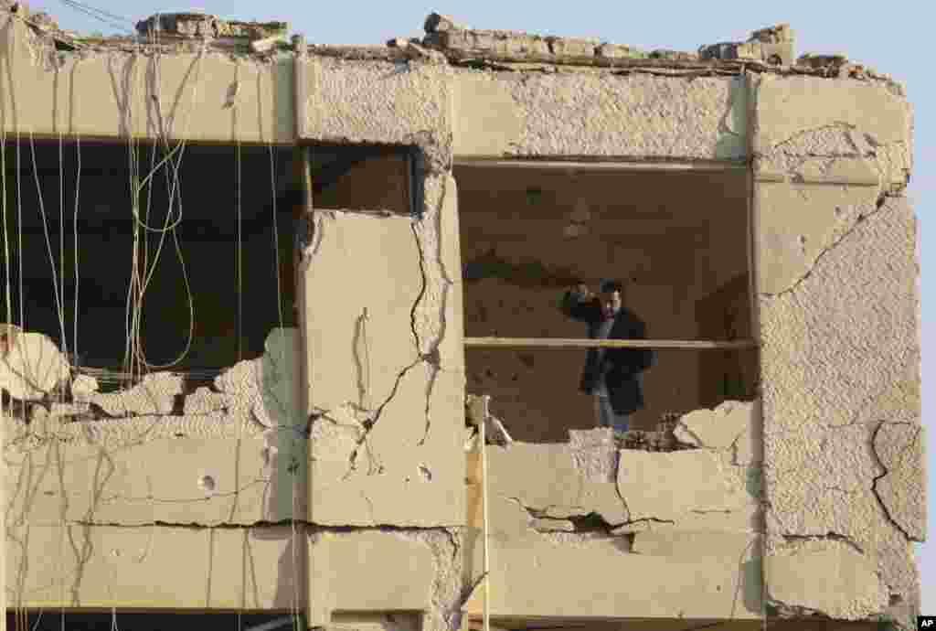 Polisi Mesir berpakaian preman berdiri di luar gedung keamanan nasional yang rusak akibat serangan bom di daerah Shubra el-Kheima di Kairo, yang melukai beberapa orang (20/8). (AP/Amr Nabil)