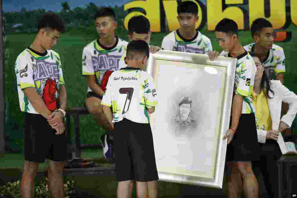Coach Ekkapol Janthawong, left, and the 12 boys pay their respect and thanks as they hold a portrait of Saman Gunan, the retired Thai SEAL diver who died during their rescue attempt, during a press conference in Chiang Rai, northern Thailand.