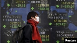 A pedestrian walks past an electronic board showing the stock market indices of various countries outside a brokerage in Tokyo, Japan, Feb. 3, 2016.