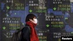 FILE - A pedestrian walks past an electronic board showing the stock market indices of various countries outside a brokerage in Tokyo, Japan, Feb. 3, 2016.