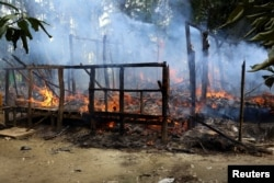 FILE - A house is seen on fire in Gawduthar village, Maungdaw township, in the north of Rakhine state, Myanmar, Sept. 7, 2017.