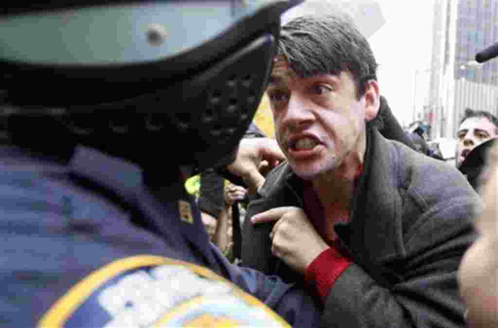 A demonstrator affiliated with the Occupy Wall Street yells at a New York City police officer outside Zuccotti Park, Tuesday, Nov. 15, 2011 in New York. Hundreds of police officers in riot gear before dawn Tuesday raided the New York City park where