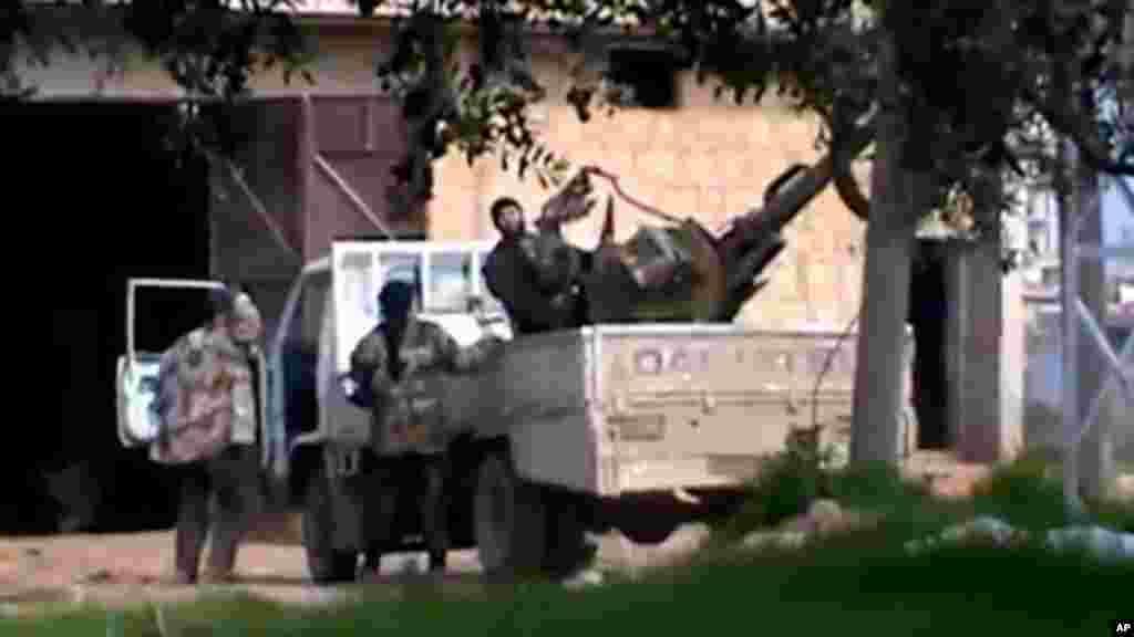 In this image taken from video obtained from the Shaam News Network, which has been authenticated based on its contents and other AP reporting, A Free Syrian Army fighter stands on a vehicle as he holds his weapon in Taftanaz village, Idlib province, nort