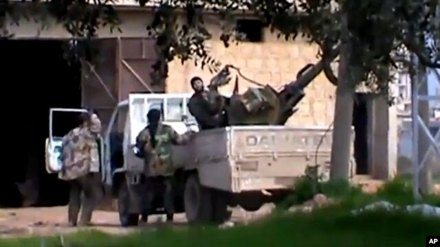 In this image taken from video obtained from the Shaam News Network, which has been authenticated based on its contents and other AP reporting, a Free Syrian Army fighter stands on a vehicle as he holds his weapon in Idlib province.