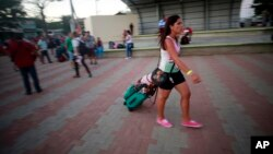 A Cuban migrant walks to a government organized bus that will take her and other Cuban migrants to the airport in La Cruz, Costa Rica, Tuesday, Jan. 12, 2016.