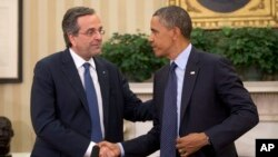 President Barack Obama shakes hands with Greek Prime Minister Antonis Samaras during their meeting in the Oval Office of the White House in Washington, Aug. 8, 2013.