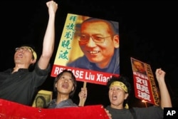 "FILE - Pro-democracy protesters raise pictures of Chinese dissident Liu Xiaobo with Chinese words reading: ""Release Liu Xiaobo"" during a demonstration outside the China's Liaison Office in Hong Kong, Oct. 8, 2010."