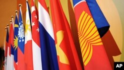The Association of the Southeast Asian Nations (ASEAN) flag, right, leads the flags of the 10 member countries during the ASEAN Regional Forum meeting.