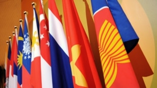 FILE - The Association of the Southeast Asian Nations (ASEAN) flag, right, leads the flags of the 10 member countries during the ASEAN Regional Forum meeting in Singapore.
