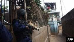 Police officers take cover during a mutiny of troops at a military camp near Madagascar's main airport, in Antananarivo, July 22, 2012.