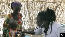 A Turkana woman holds a young child as both are examined for malnutrition by a World Vision nurse at a feeding and treatment center in Lokori, Kenya, July 28, 2011