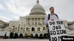 Seorang pegawai federal yang terkena 'furlough' (dirumahkan), memegang kertas bertuliskan pesan kepada para anggota kongres di depan Gedung Capitol, Washington DC, pasca penutupan operasi pemerintah AS (1/10). Penutupan pemerintah AS yang terjadi untuk pertama kalinya dalam 17 tahun terakhir ini, mengakibatkan sekitar sekitar 800 ribu pegawai federal dirumahkan, ditutupnya taman-taman kota dan penundaan berbagai proyek penelitian (REUTERS/Larry Downing).