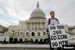 امریکی پارلیمان کی عمارت 'کیپٹ ہل' کے سامنے ایک شخص احتجاجی کتبہ لیے کھڑا ہے