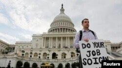 """Một công chức chính phủ liên bang, đứng trên thềm trụ sở Quốc hội, cầm tấm bảng với dòng chữ """"Xin hãy thực hiện phần việc của quý vị để tôi có thể làm công việc của tôi"""""""
