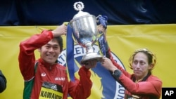 Yuki Kawauchi, left, of Japan, and Desiree Linden, of Washington, Michigan, hoist the trophy after winning the men's and women's division of the 122nd Boston Marathon, April 16, 2018, in Boston, Massachusetts.