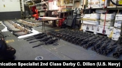 A cache of weapons is assembled on the deck of the guided-missile destroyer USS Gravely (DDG 107). The weapons were seized from a stateless dhow which was intercepted by the Coastal Patrol ship USS Sirocco on March 28.