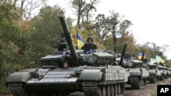 FILE - Ukrainian tanks move near Mariupol, Donetsk region, eastern Ukraine, Oct. 21, 2015.