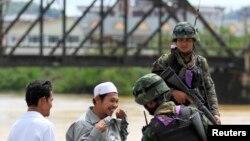 Tentara Thailand memeriksa warga di sebuah pos di propinsi Yala (28/2). Sehari setelah pemerintah Thailand menyepakati dimulainya perundingan dengan kelompok pemberontak muslim untuk pertamakalinya dalam upaya mengakhiri konflik, sebuah bom meledak di Thailand Selatan, dan melukai sedikitnya enam orang (1/3).