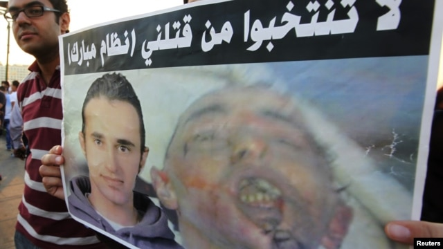 Demonstrators carry poster of Khaled Said on the second anniversary of his death by Egyptian police, Cairo, June 6, 2012.