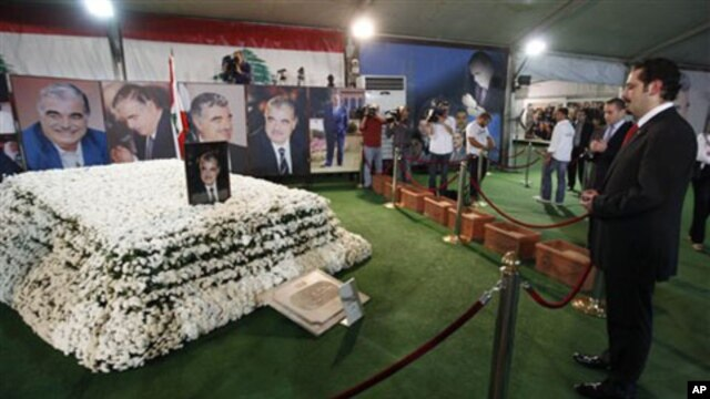 Former Lebanese Prime Minister Saad Hariri, right, the son of slain former Prime Minister Rafiq Hariri, prays at his father's grave in downtown Beirut, 09 Nov 2009