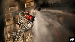 Firefighters work to douse a fire in a multi-storied office building in Dhaka, Bangladesh, March 28, 2019.