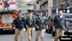 Para petugas Biro Penyidikan Federal (FBI) segera menyelidiki situasi di lokasi kejadian ledakan bom, dekat garis finish lomba marathon Boston, Massachusetts (15/4).