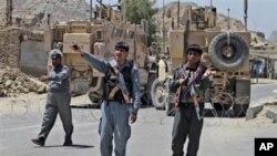 Polícias afegãos e blindados da NATO de guarda nas imediações da prisão de Kandahar, de onde se evadiram 500 prisioneiros.