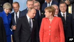 FILE - German Chancellor Angela Merkel, right, chats with Russian President Vladimir Putin after the family photo on the first day of the G-20 summit in Hamburg, northern Germany, July 7, 2017.