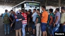 Беженцев, задержанных на границе с Венгрией, на автобусе собираются перевезти в центры временного содержания. Австрия. 29 августа 2015 г.