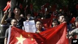中国抗议者2012年9月14日举着反日标语在日本驻北京使馆前连续第四天示威。