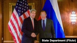 FILE - U.S. Secretary of State John Kerry shakes hands with Foreign Minister Sergey Lavrov. The two officials talked by phone Friday about widening international political talks on Syria.