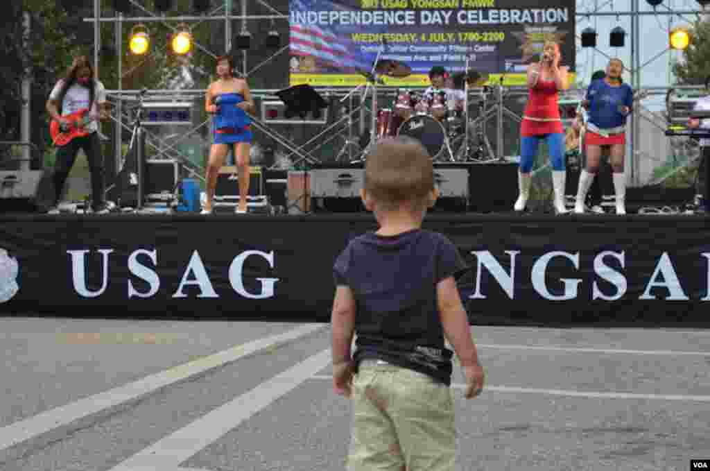 "Ayden Massey, 19 months old, of Seoul, watches the band ""Absolute"" from the Philippines performing at 4th of July celebrations at US Army Garrison-Yongsan in South Korea, July 4, 2012. (S.L. Herman/VOA)"
