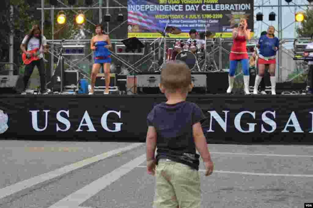 Tại Seoul, bé Ayden Massey, 19 tháng tuổi, xem ban nhạc chơi nhân Lễ Độc lập trong căn cứ quân sự Hoa Kỳ tại Nam Triều Tiên, 4/7/2012. (S.L. Herman/VOA)