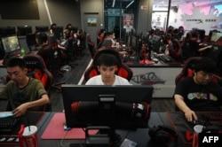 Para penggemar game online, tengah bermain di sebuah cafe internet di Beijing, 10 September 2021. (AFP)