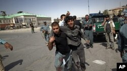 An Afghan policeman helps a wounded man away from the site of an attack at a Kabul police station, June 18, 2011