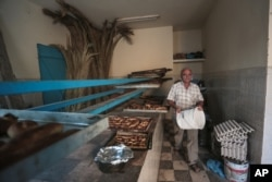Yofel Sabbagh, 46, walks inside a bakery as he prepares Challah, a special Jewish bread, on the eve of Shabbath, at Hara Kbira, on the island of Djerba, southern Tunisia, Oct. 30, 2015.