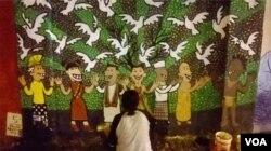 Seorang seniman mural menggambar di dinding Stadion Kridosono, Yogyakarta berisi pesan damai dan kesetaraan. (Foto: VOA/Nurhadi-dok/ilustrasi)
