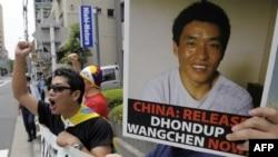 """Para pendemo dari """"Mahasiswa untuk Pembebasan Tibet Jepang,"""" meneriakkan slogan menuntut pembebasan sutradara film asal Tibet, Dhondup Wangchen, yang wajahnya tampak di poster. Demonstrasi berlangsung di depan Kedutaan Besar China di Tokyo, 1 Agustus 2009."""
