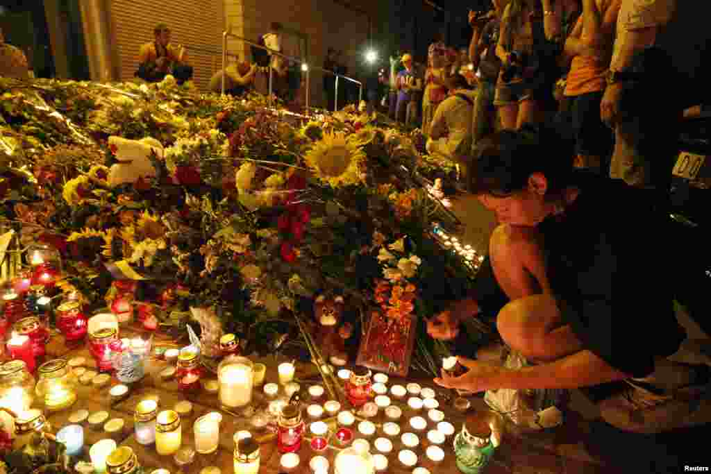 People bring flowers and candles to the Dutch embassy in Kyiv, Ukraine, to commemorate the victims of the Malaysia Airlines Boeing 777 plane crash.