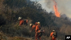 Firefighters work to remove brush to prevent a wildfire from spreading along a remote oil field access road in Ventura County, California, Dec. 26, 2015.
