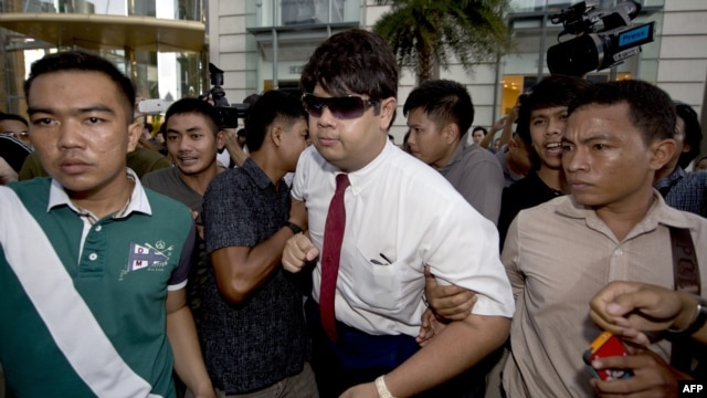 Thai policemen arrest an anti-coup protester (C) during a demonstration at a shopping mall in Bangkok, June 22, 2014.